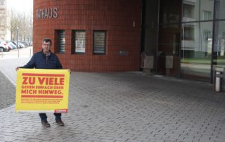 """Frank Schönfeld (Kreistagsabgeordneter) mit dem Bodenaufkleber der Aktion """"Vorsicht, Vorurteile"""" (2021) vor dem Rathaus Hennigsdorf"""